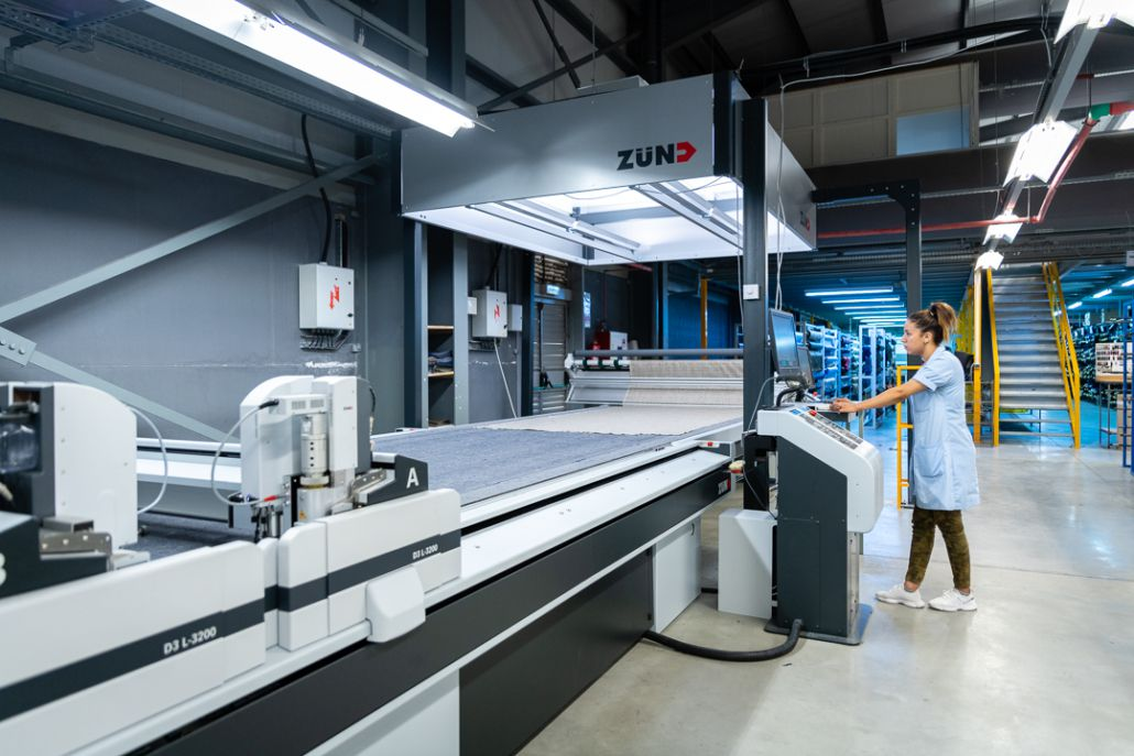 Young woman operating a machine in Tailoring factory